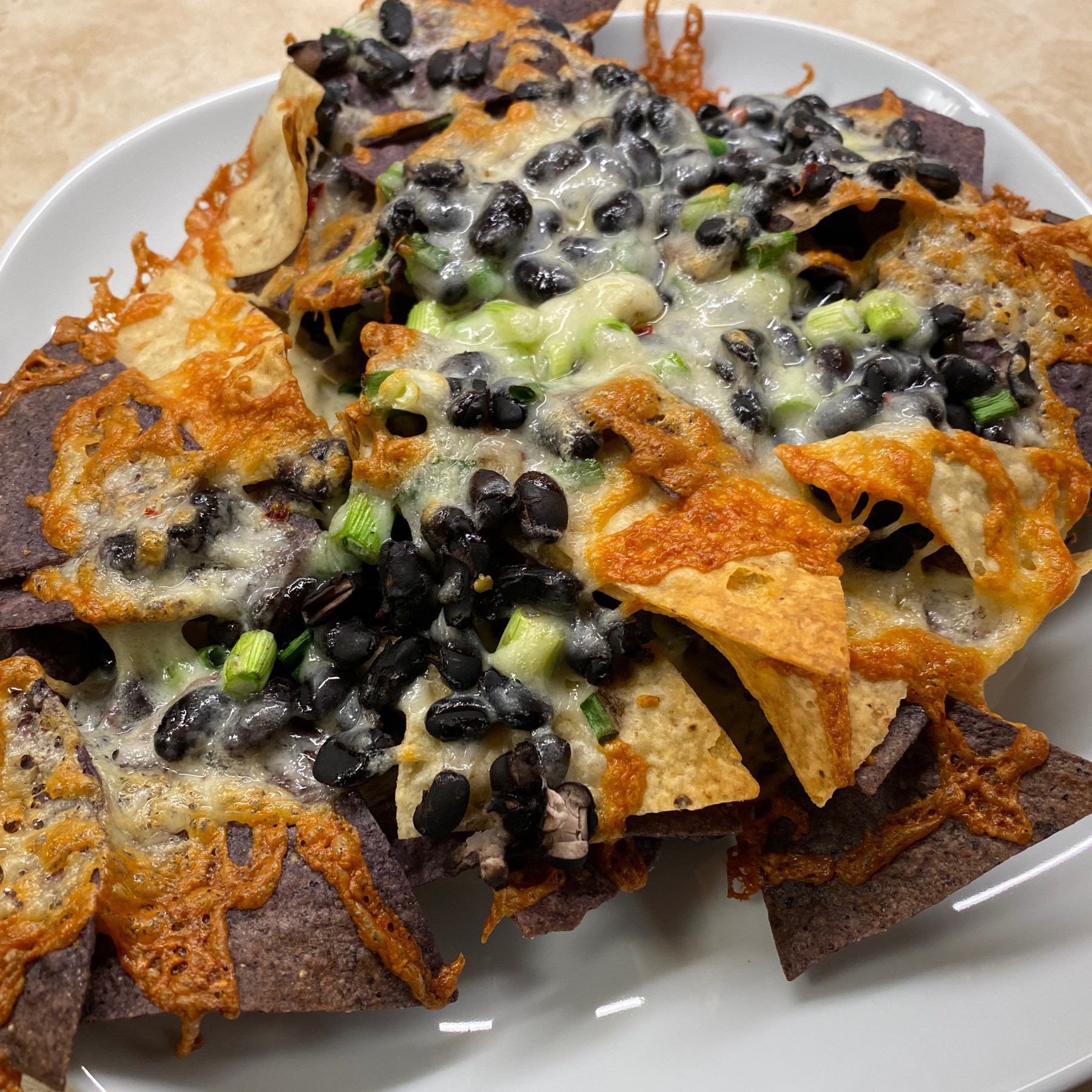 Nachos with black beans and cheese on plate.
