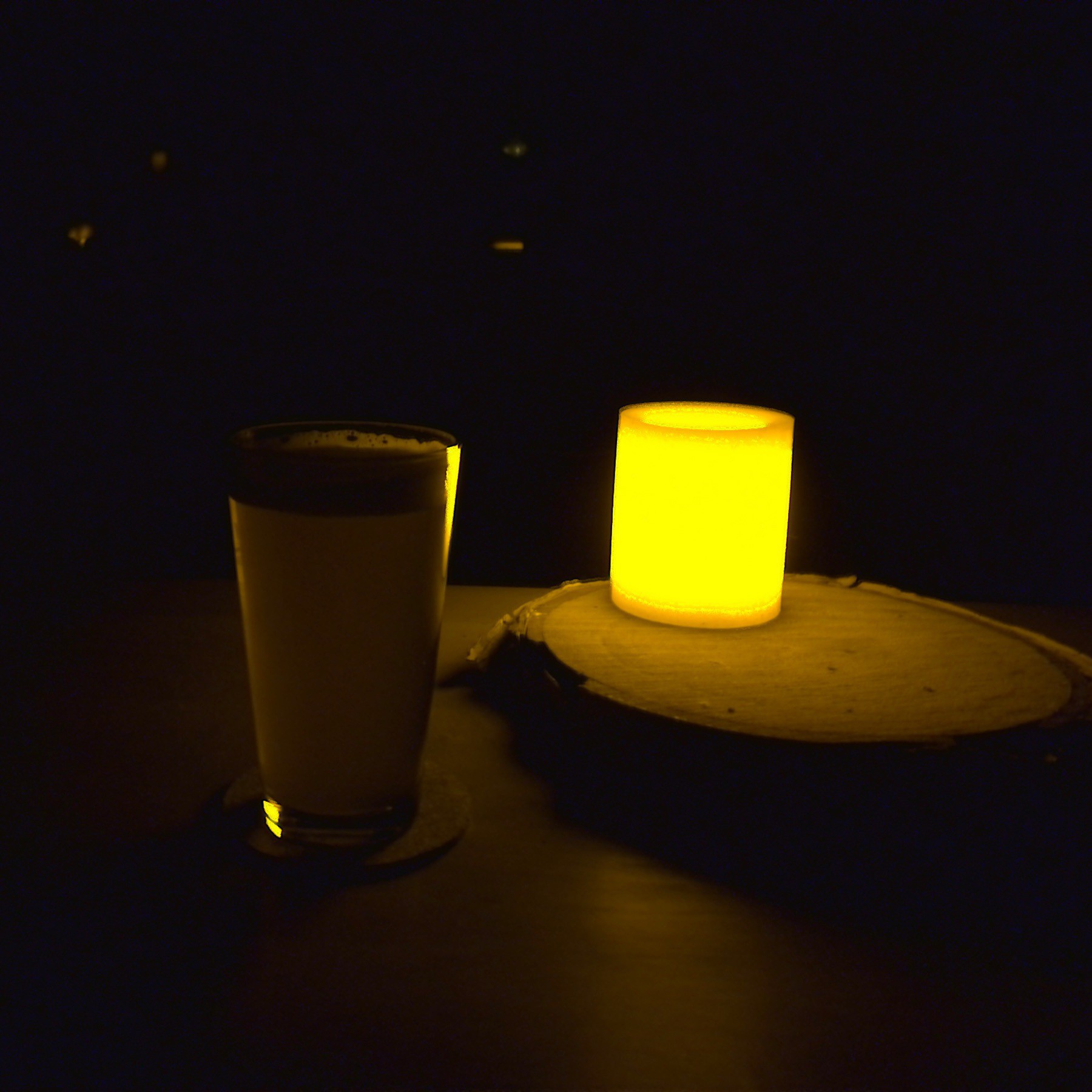 Glass if beer beside LED candle.