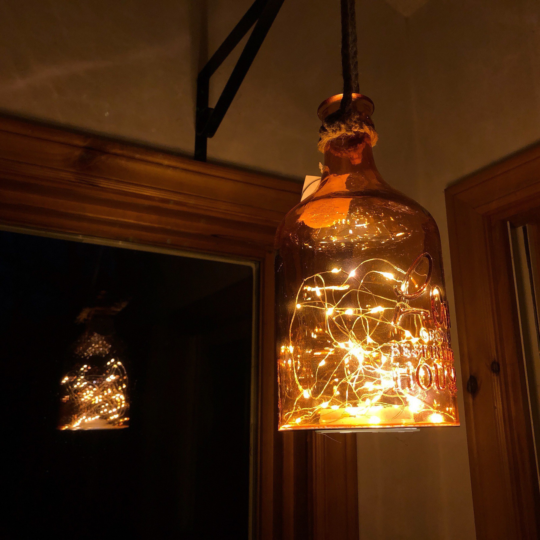 LED ights in bottle hanging from hook.