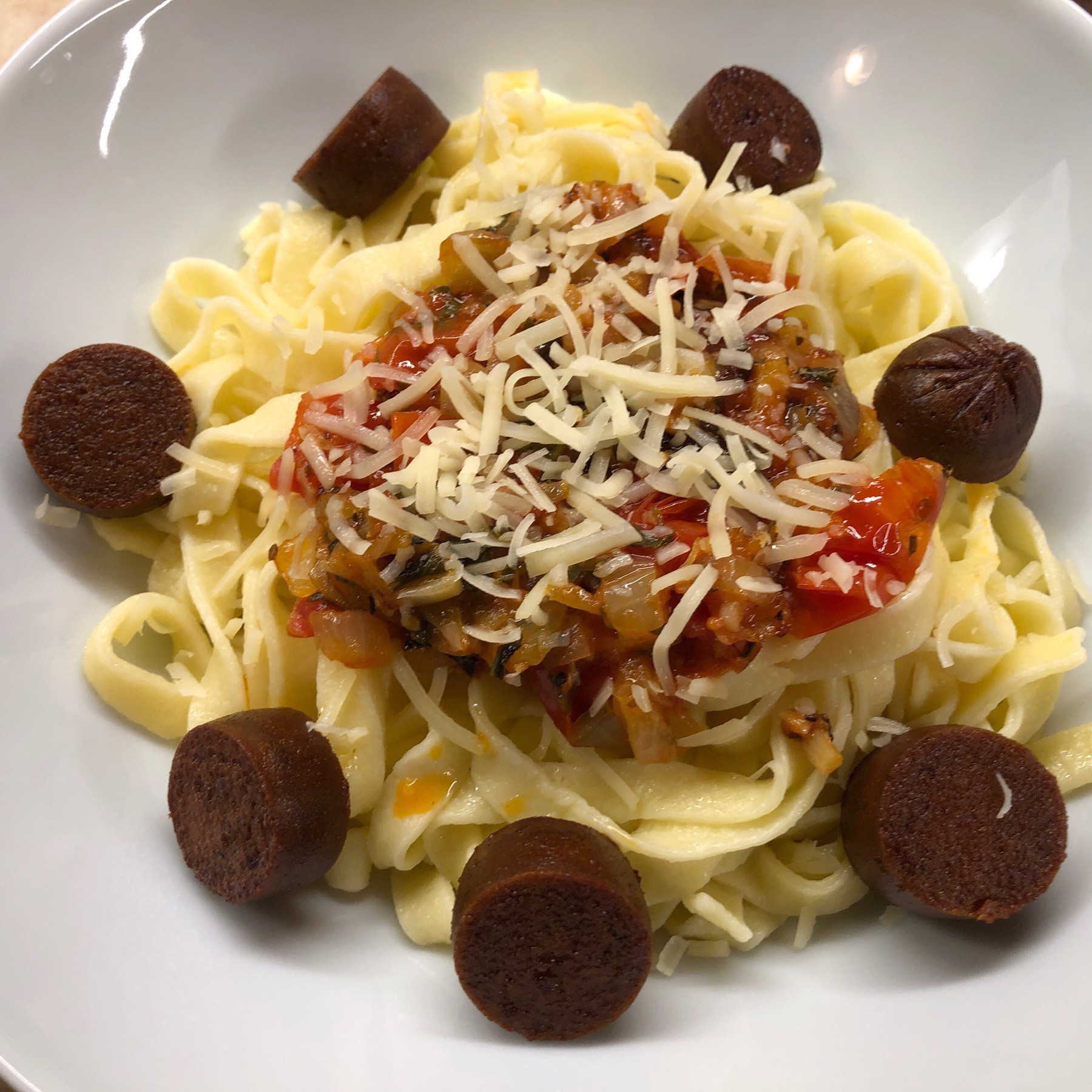 Pasta and sauce and veggie sausages in bowl.