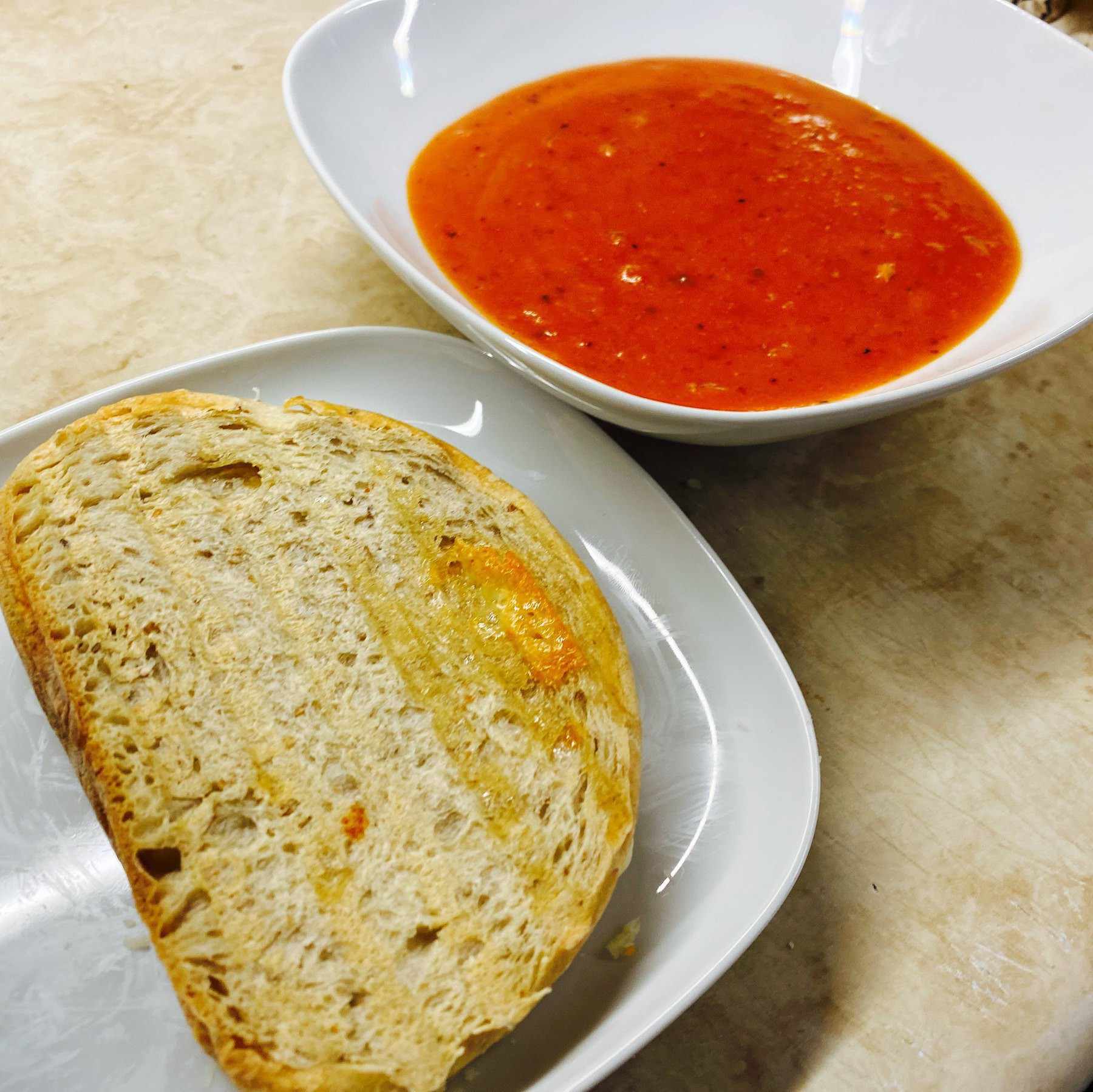 Grilled cheese sandwich on plate and bowl of tomato soup.