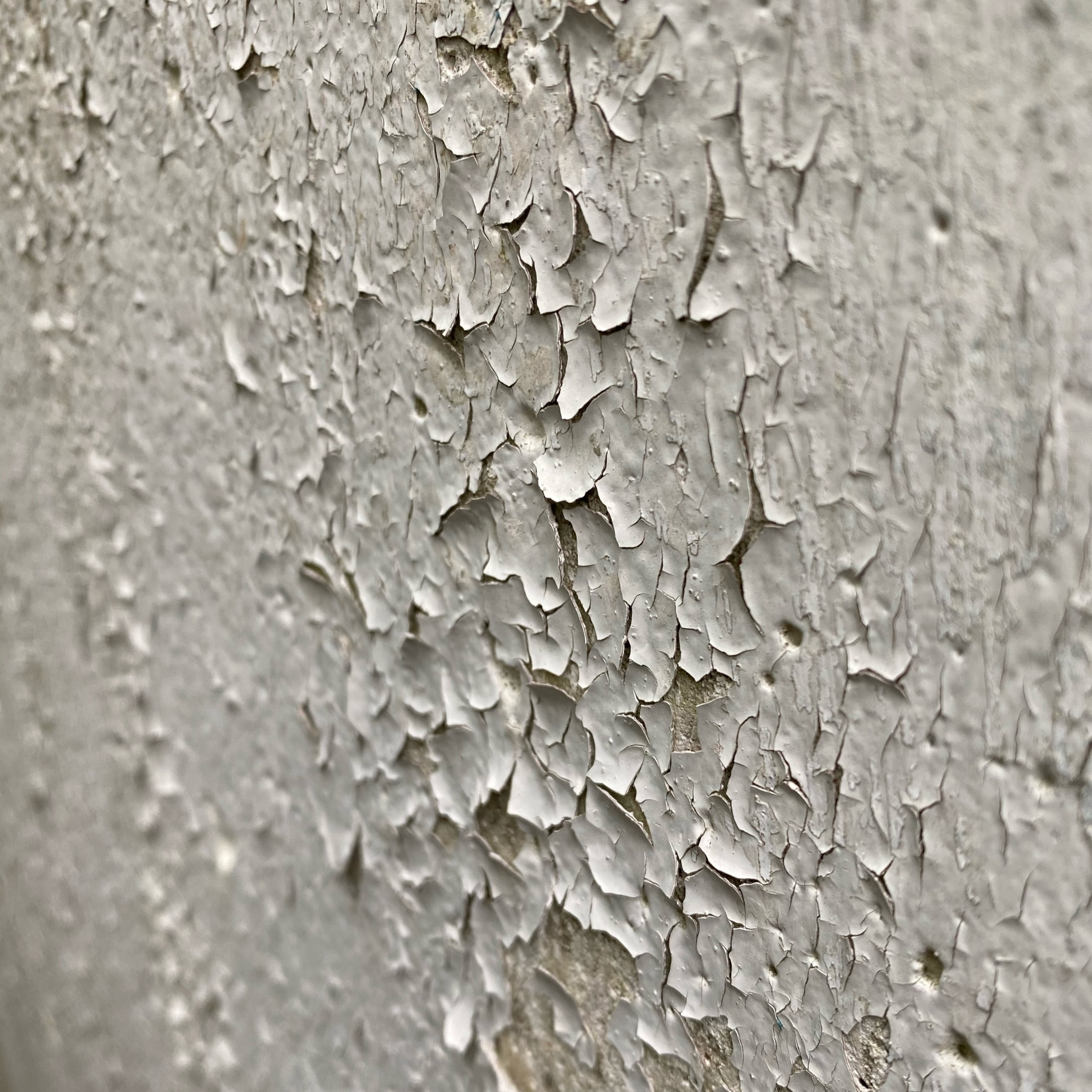 Paint flaking on concrete wall.