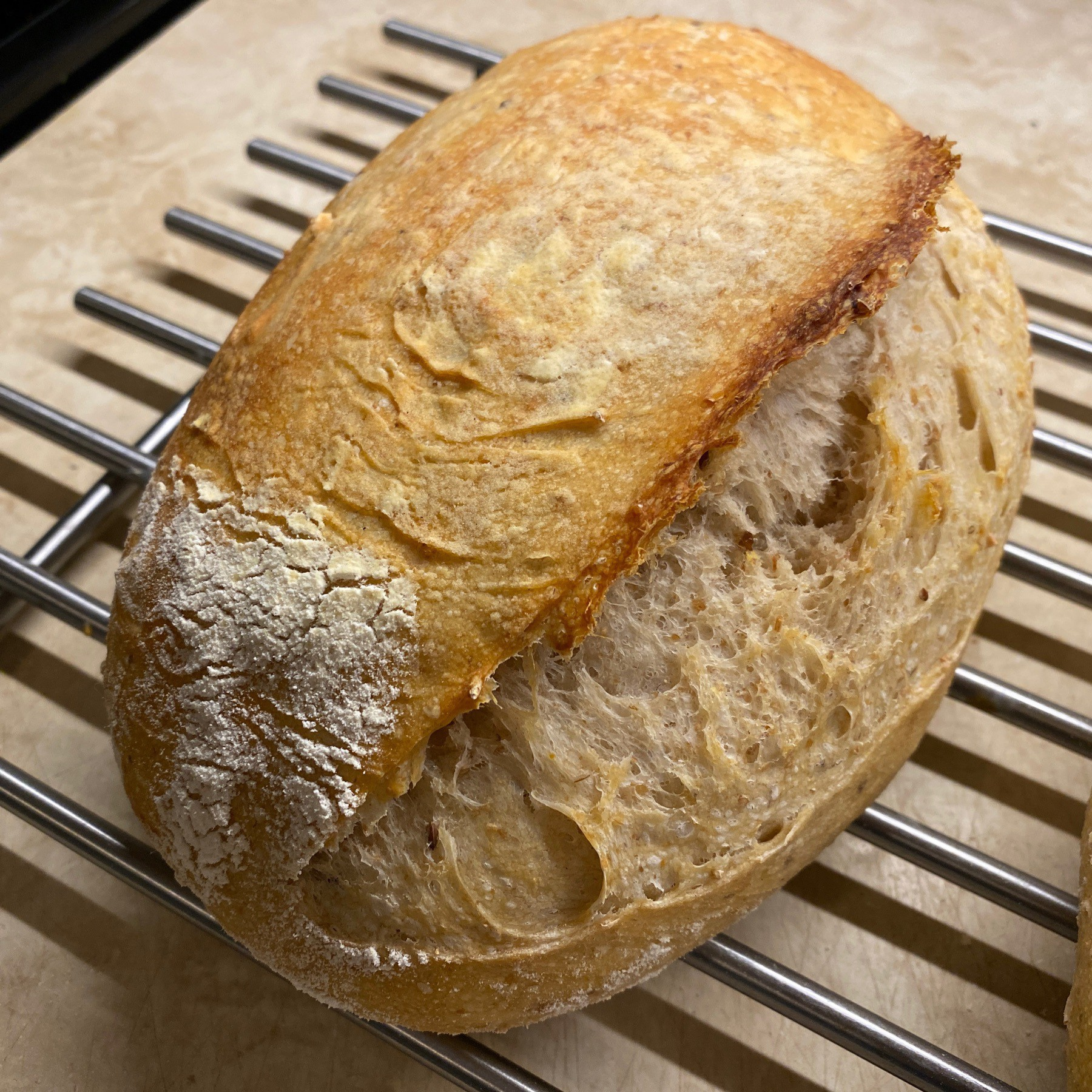 Sourdough bread loaf cooling on metal rack.