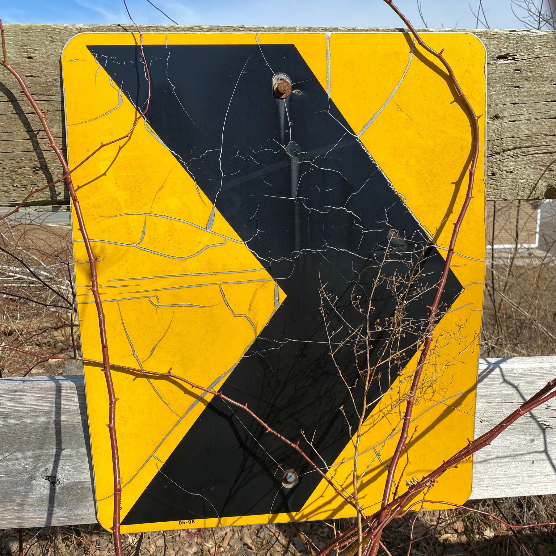 Arrow on sign on wooden fence.