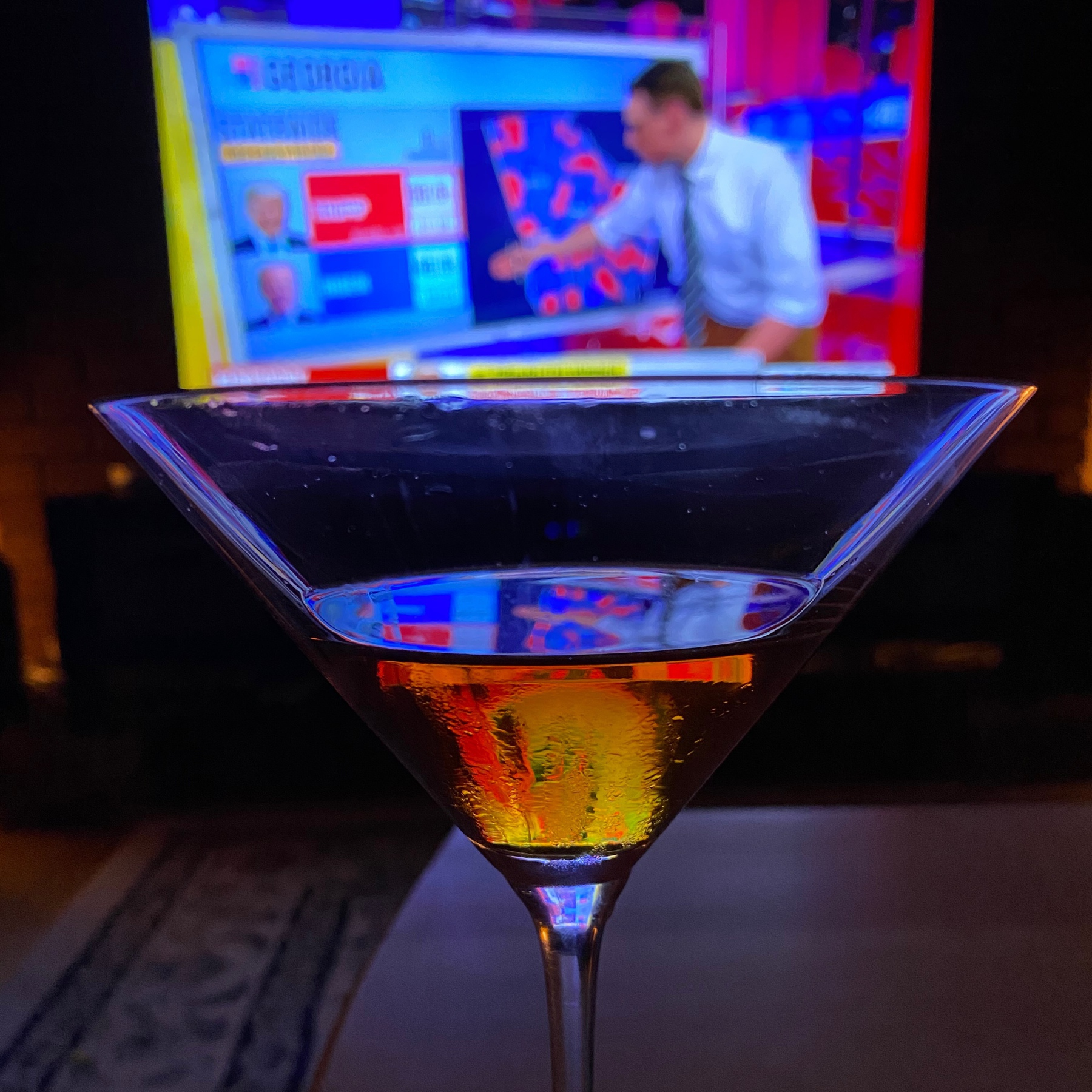 Martini glass with television in background.
