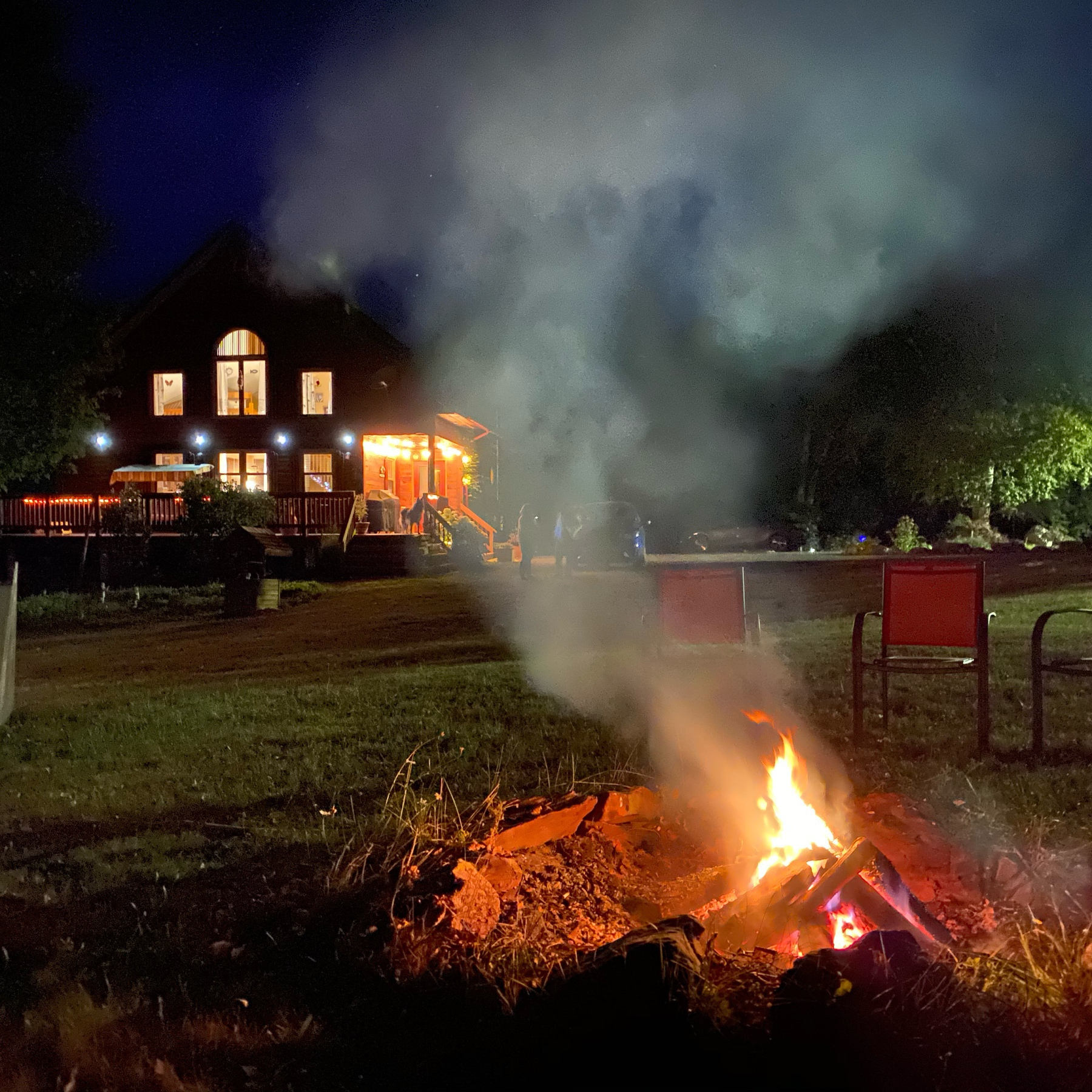 House and fire in pit at night.