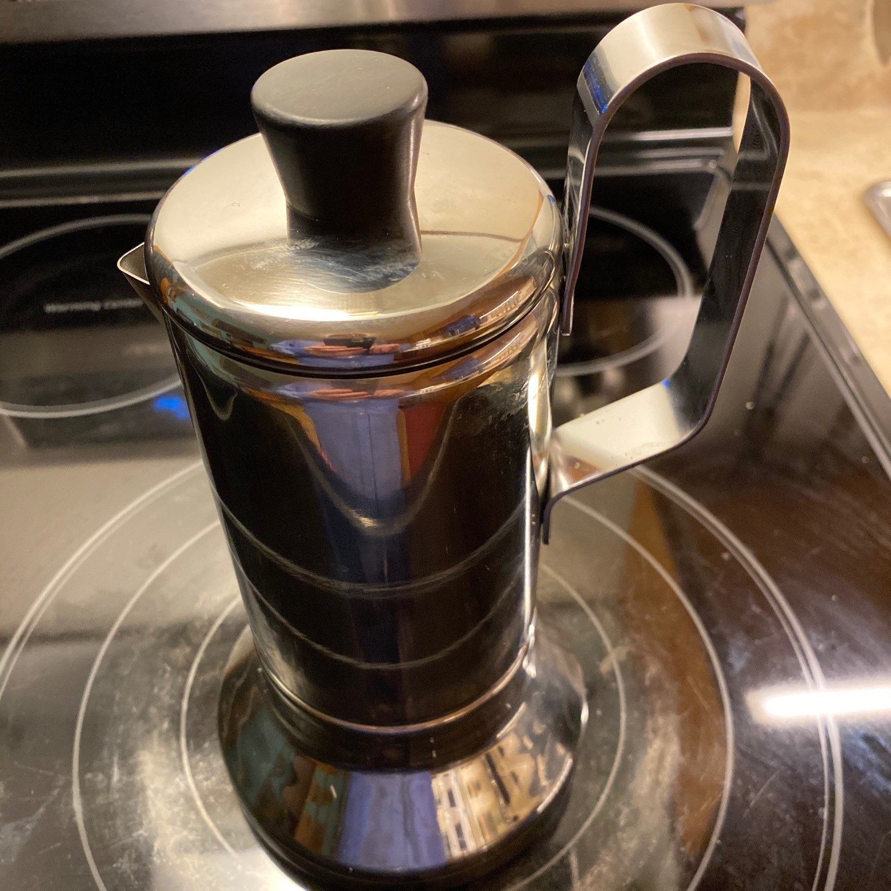 Espresso maker on stove burner.