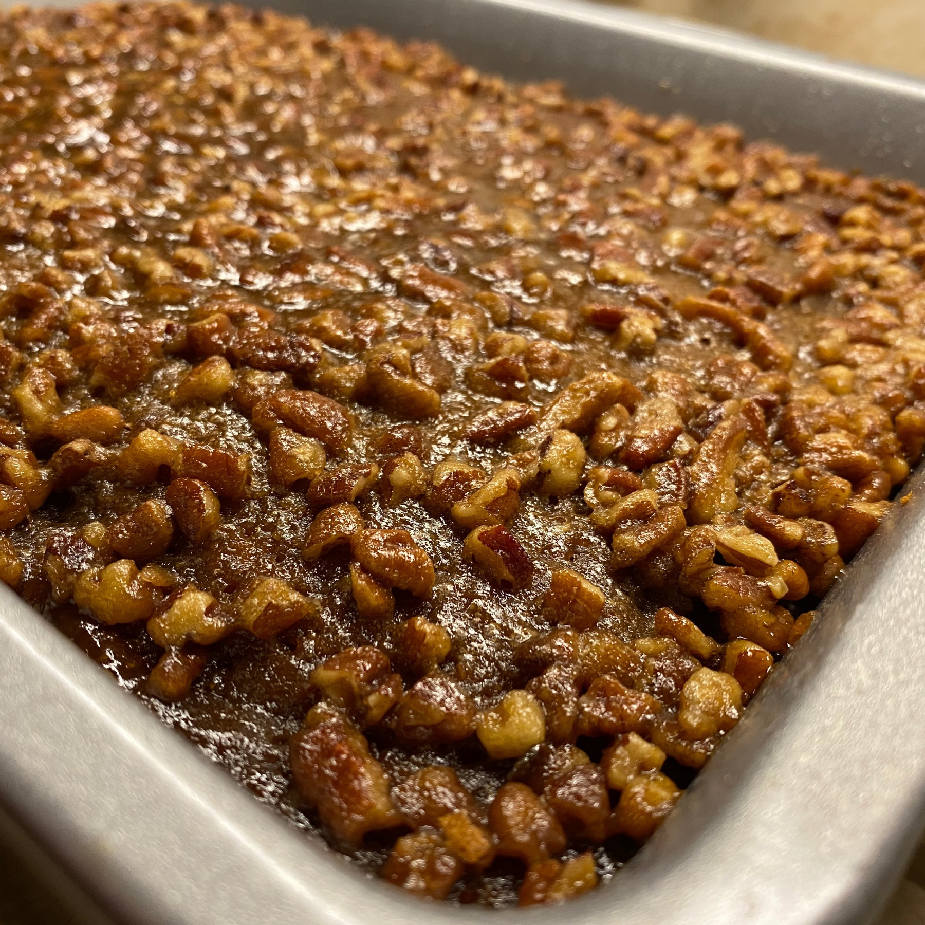 Pecans in glaze on top of cake.