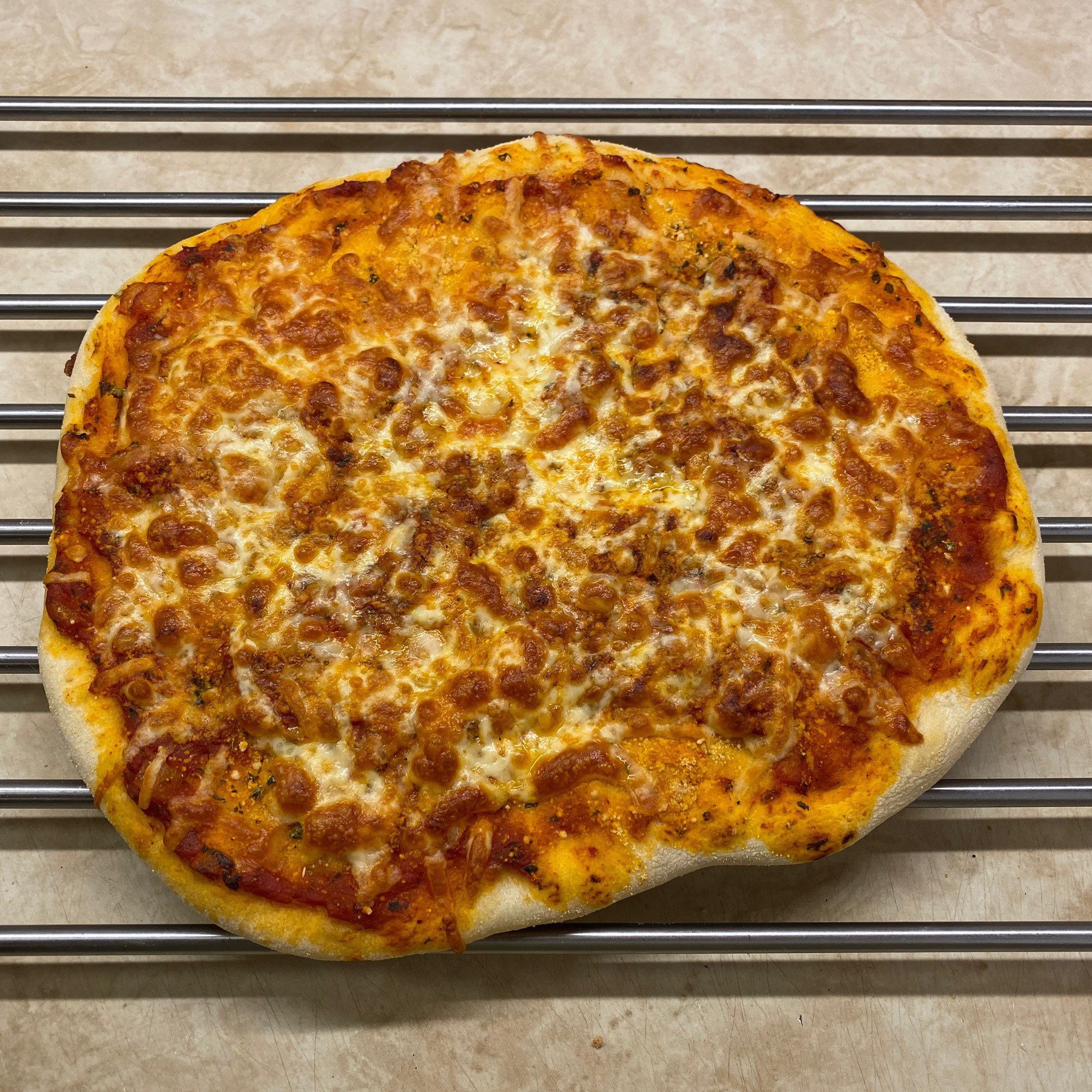 Cheese pizza cooling on rack.