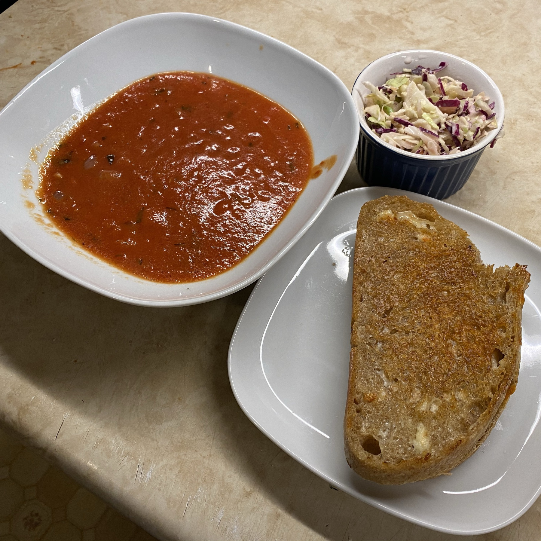 Bowl of tomato soup, grilled cheese sandwich on plate, and bowl of coleslaw.