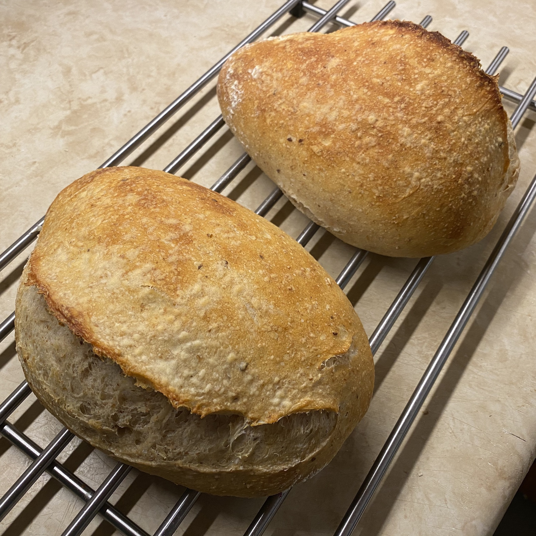 Sourdough loaves cooling on metal rack.