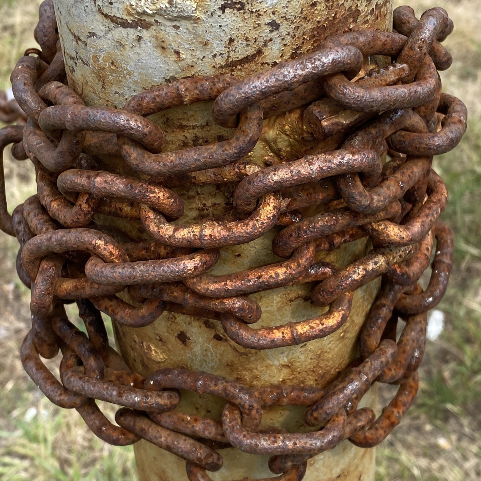 Rusting chain wrapped around metal post.