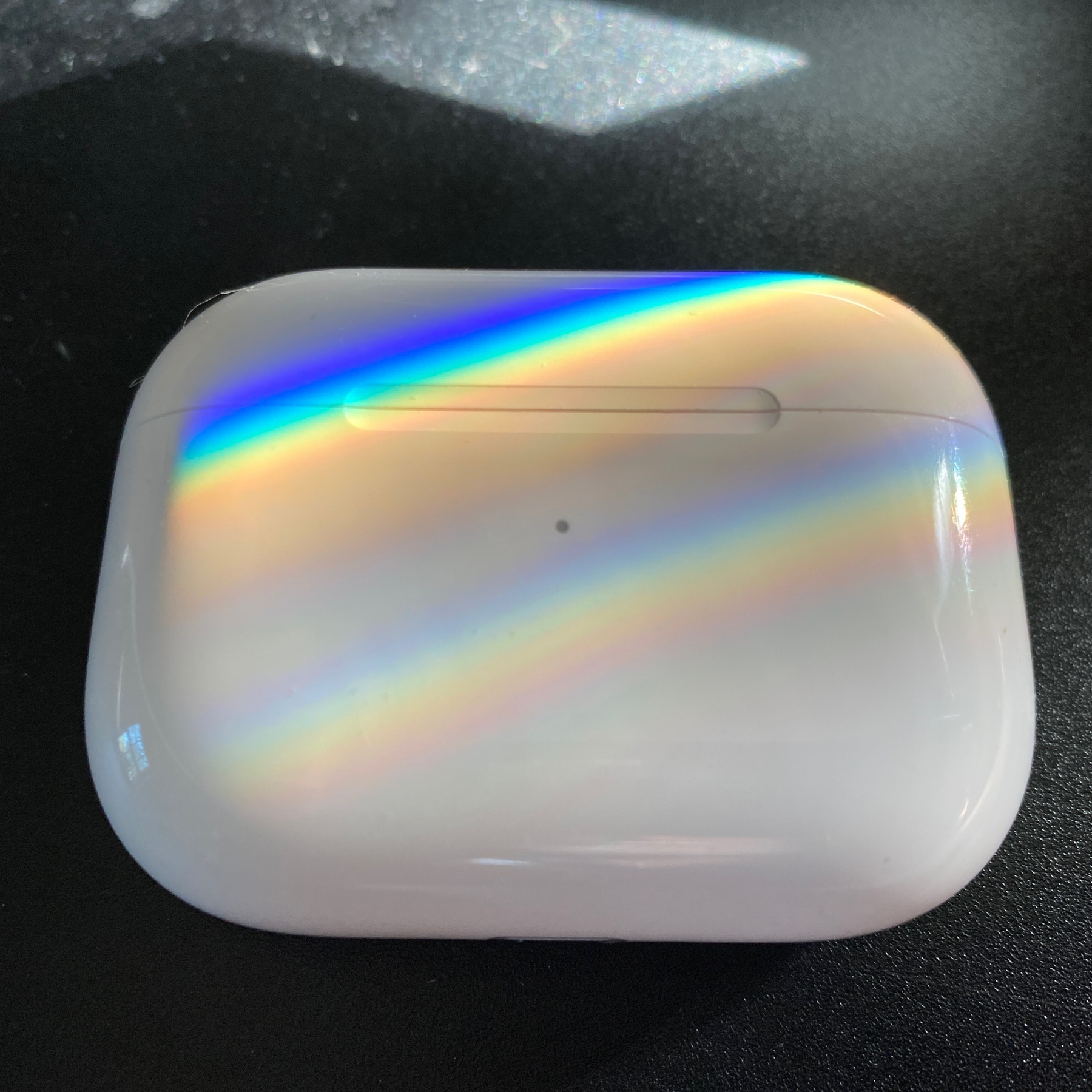 AirPods Pro case with refracted rainbow stripes on it.