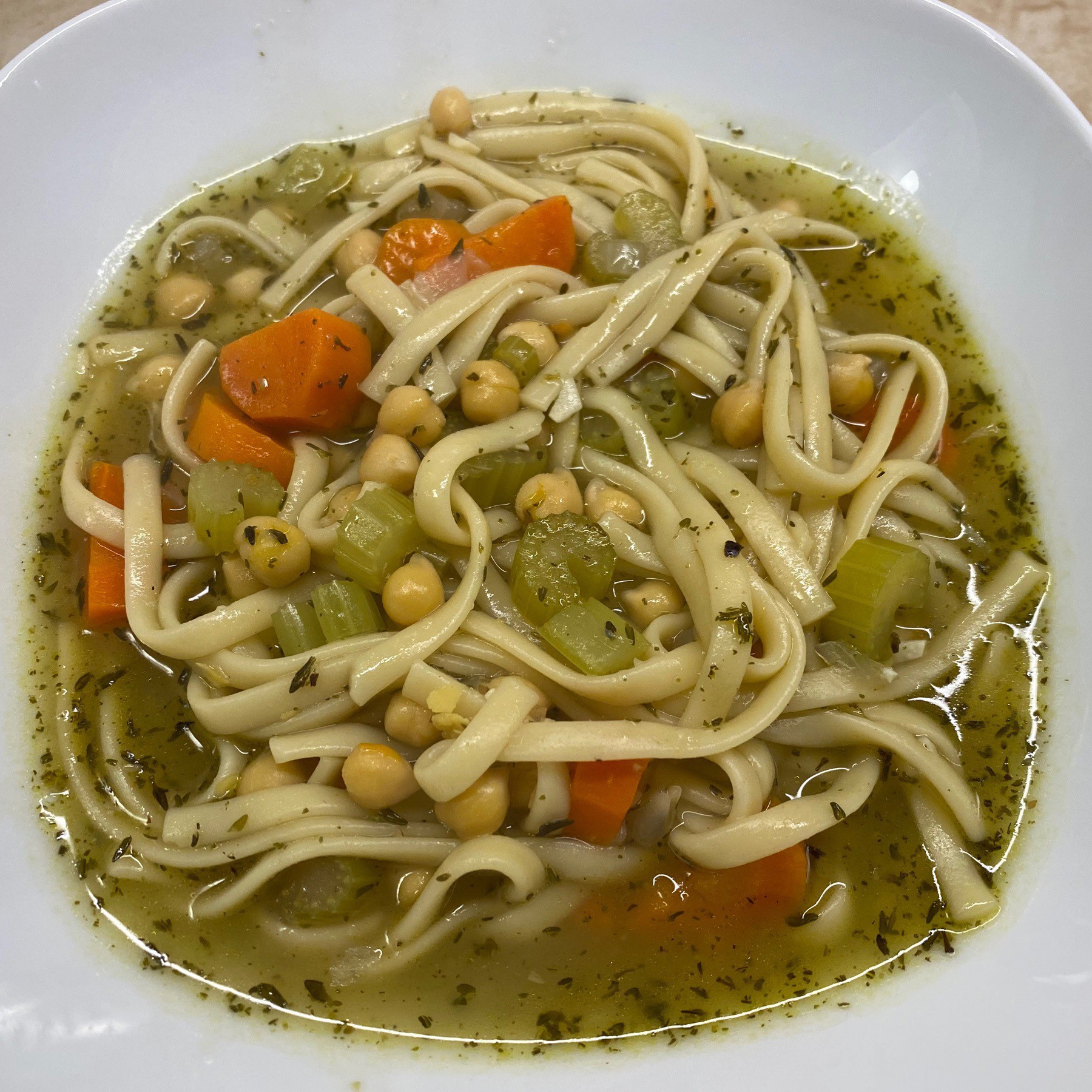 Bowl of soup with noodles, chickpeas, carrots, and celery.