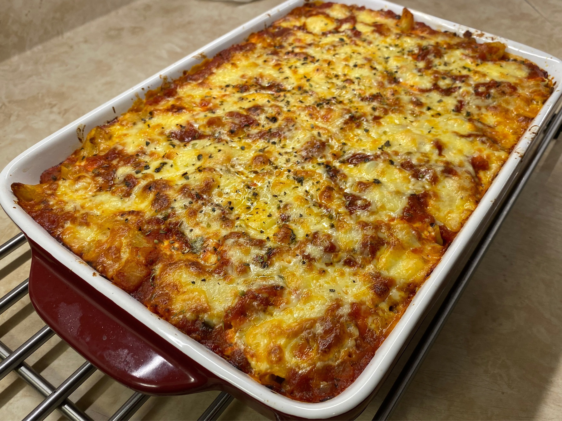 Baked pasta with cheese on top sitting on metal rack.