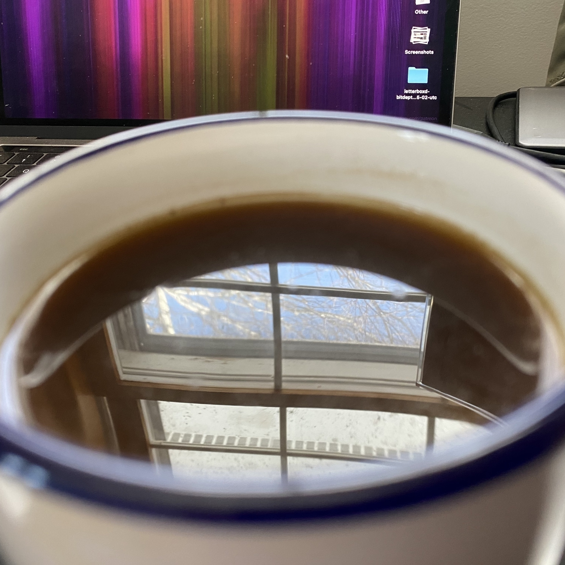 Window reflected in coffee in mug.