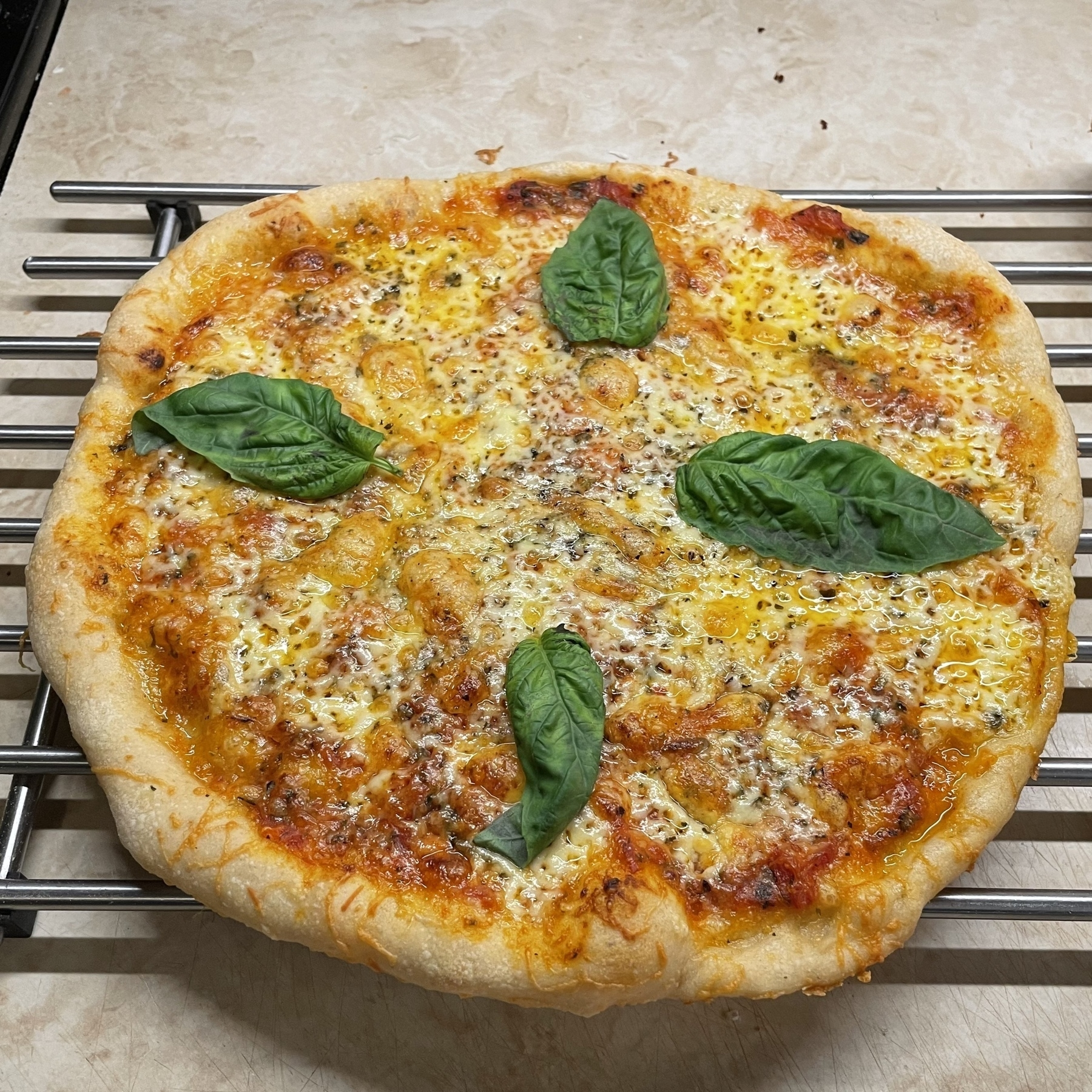 Cheese pizza on metal rack.