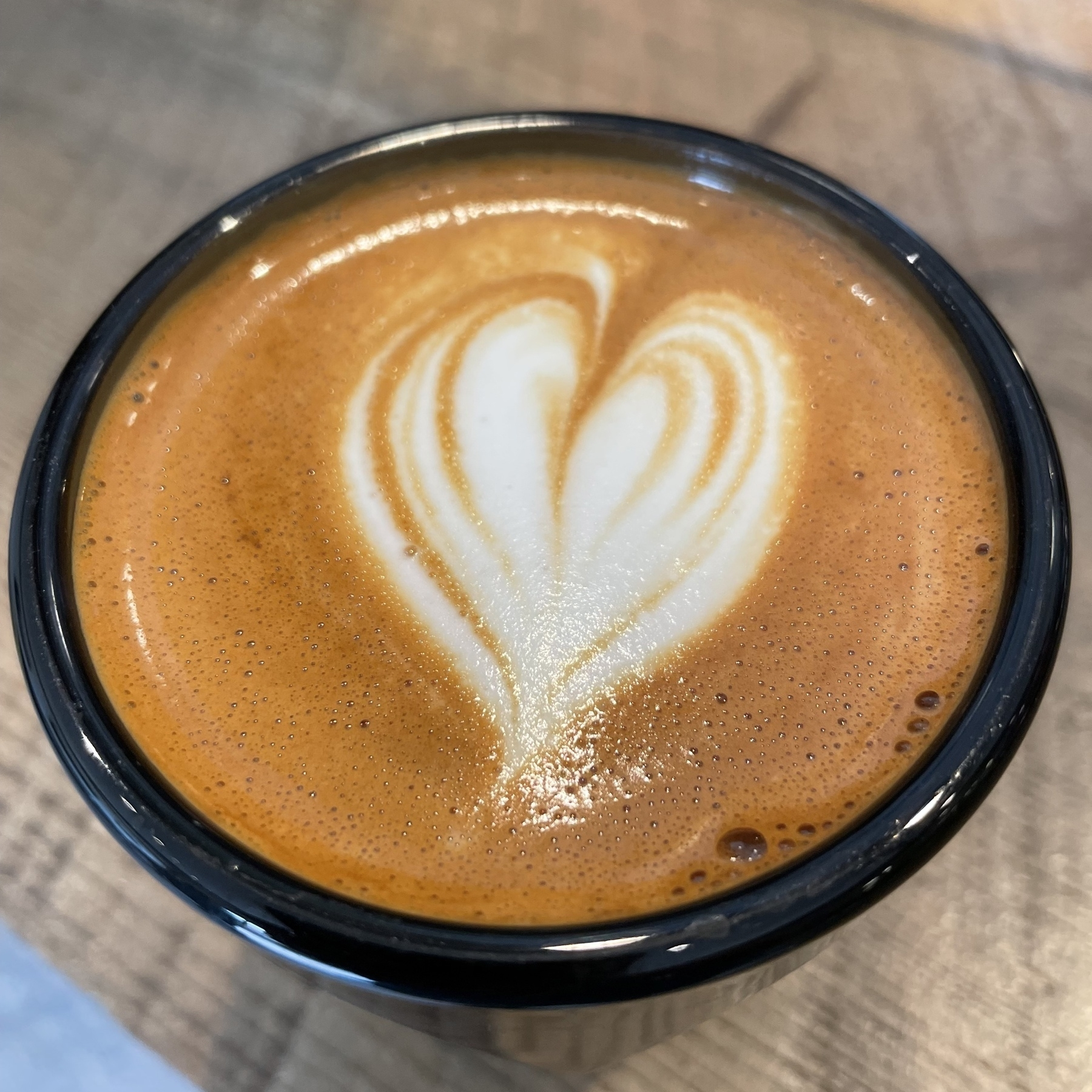Heart pattern in milk at top of coffee in cup.
